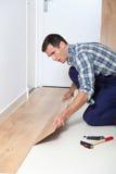 Man putting floating floor. Closeup of artisan installing flooring in room Royalty Free Stock Images