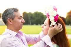 Man putting flowers wreath on his girlfriends head. Romantic present and scene stock image