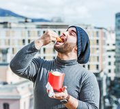 Man putting french fries in his mouth - urban background Royalty Free Stock Photos