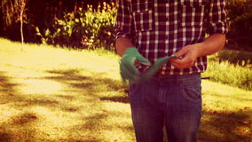Man putting gardening glove in the park stock video