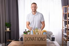 Man Putting Groceries In Donation Box. Young Man Putting Groceries In Donation Box Over Wooden Desk royalty free stock photography
