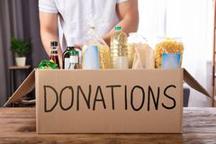 Man Putting Groceries In Donation Box. Young Man Putting Groceries In Donation Box Over Wooden Desk stock images