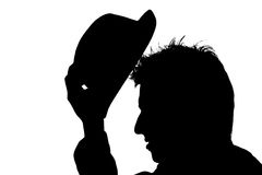 Man putting hat on his head � silhouette. Young man putting hat on his head � silhouette royalty free stock photos