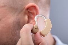 Man Putting Hearing Aid In His Ear. Close-up Of A Man`s Hand Putting Hearing Aid In His Ear stock photos