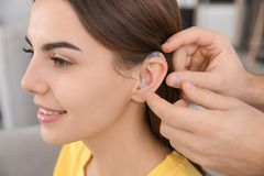 Man putting hearing aid in woman`s ear, closeup. Man putting hearing aid in woman`s ear indoors, closeup stock photography