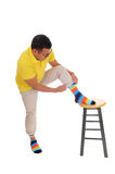 Man putting on his colorful socks. A middle age Hispanic man lifting up his leg on a chair and putting on his colorful socks, isolated for white background stock photography