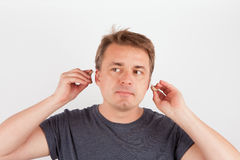 Man putting on his hearing aids. Man putting hearing aids into ears royalty free stock images