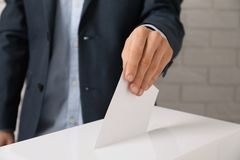 Man putting his vote into ballot box against brick wall. Closeup royalty free stock photography