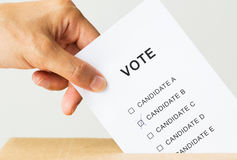 Man putting his vote into ballot box on election. Voting, civil rights and people concept - close up of male hand putting vote into ballot box on election Royalty Free Stock Images