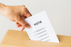 Man putting his vote into ballot box on election. Voting, civil rights and people concept - close up of male hand putting vote into ballot box on election Royalty Free Stock Image