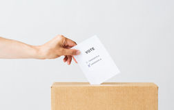 Man putting his vote into ballot box on election. Voting, civil rights and people concept - male hand putting vote with two candidates into ballot box on Stock Image