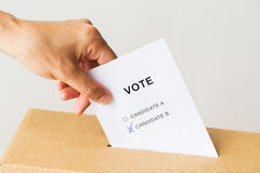 Man putting his vote into ballot box on election. Voting, civil rights and people concept - male hand putting vote with two candidates into ballot box on Royalty Free Stock Photo