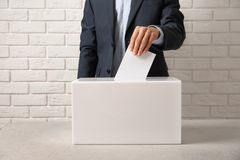Man putting his vote into ballot box on table against brick wall. Closeup royalty free stock photos