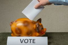 Man putting his vote into piggi-bank on table royalty free stock photo