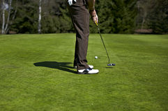 Man putting at a hole at the golf course Stock Photos