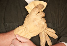 Man Putting on Leather Construction Gloves Stock Photography