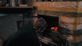 Man Putting Log Onto Wood Burning Stove, Holiday And Lifestyle Concept stock footage