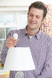 Man Putting Low Energy LED Lightbulb Into Lamp At Home Royalty Free Stock Photos