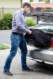 Man putting luggage into car trunk. Vertical Stock Photography