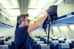 Man putting luggage on the top shelf on airplane. Travel concept royalty free stock photos