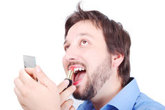 Man putting make-up on his lip. Man is putting make up on  his lips with happy expression on face Royalty Free Stock Images