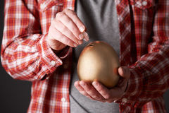 Man Putting Money Into Golden Egg Shaped Money Box Stock Photos