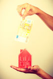 Man putting money into house piggybank Royalty Free Stock Photos