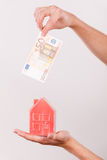 Man putting money into house piggybank Stock Photography