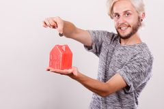 Man putting money into house piggybank Royalty Free Stock Images