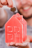 Man putting money into house piggybank Stock Image