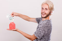 Man putting money into house piggybank Royalty Free Stock Image