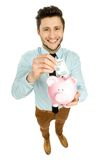 Man putting money in piggy bank Royalty Free Stock Images
