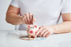 Man putting money into piggy bank Royalty Free Stock Photo