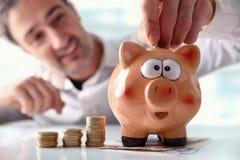 Man putting money into piggy bank Stock Photography