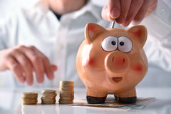 Man putting money into piggy bank horizontal composition Royalty Free Stock Photos