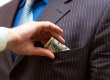 Man putting money into suit pocket Stock Photo