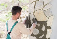 Man putting natural stones on a wall Stock Photography