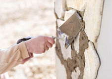 Man putting natural stones on a wall Royalty Free Stock Image