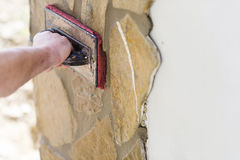 Man putting natural stones on a wall Royalty Free Stock Photo