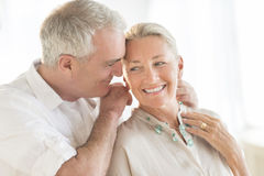 Man Putting Necklace Around Woman's Neck At Home Royalty Free Stock Photography