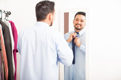 Man putting on necktie in a dressing room Royalty Free Stock Photography
