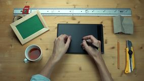 Man putting off sticky note with question sign using graphic tablet at desk. Man putting off sticky note with question sign using digital graphic tablet at stock video footage
