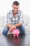 A man putting a pennie in a piggy bank Stock Images