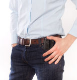 Man putting phone in pocket. Attractive young man in jeans and shirt putting cell phone in front pocket, against white background Royalty Free Stock Photo