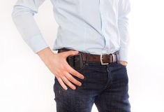 Man putting phone in pocket. Attractive young man in jeans and shirt putting cell phone in front pocket, against white background Royalty Free Stock Photography