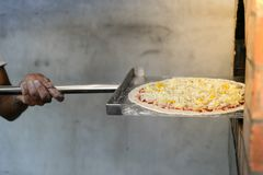 Man putting pizza baking sheet in oven at restaurant kitchen. stock images