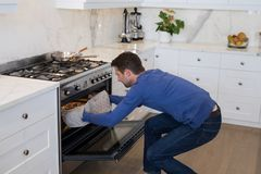 Man putting pizza into oven in kitchen. At home Stock Image