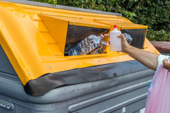 Man putting plastic waste in recycling bin Royalty Free Stock Images