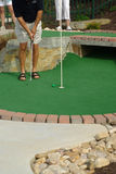 Man putting on a Putt Puut course. Man sinking a put on a putt putt course Royalty Free Stock Photography