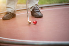 Man is putting a red golf ball with his iron racket Stock Image